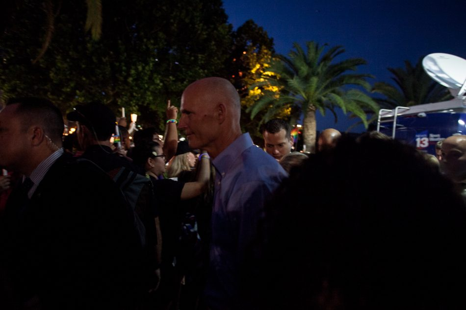 Governor Rick Scott is quickly ushered out from the candle light vigil at Lake Eola on June 19 2016.